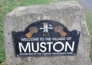 Muston Road sign with its scarecrow